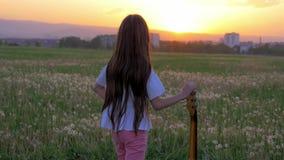 No músico pequeno do por do sol a menina no meio do campo guarda a guitarra da mão e a vista na distância na cidade pensamento do filme