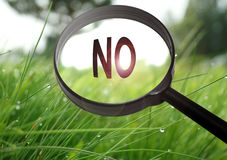 No. Magnifying glass with the word no on grass background. Selective focus Royalty Free Stock Photos