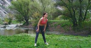 No meio de um campo verde com a mulher atrativa da paisagem bonita com um corpo apto que faz seus exercícios do exercício filme