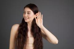 No mogę słuchać ciebie Piękna młoda pozytywna dziewczyna z długim brunetka włosy z ręką blisko ucho zdjęcie stock