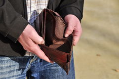 No money. Man is lokking for money in empty wallet Stock Photo