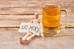 No more alcohol drinking concept. Male wooden figure, message, glass of beer, wooden background Royalty Free Stock Photography