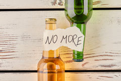 No more alcohol and drunkenness. Message, two bottles, old wooden background Stock Images