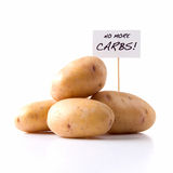 No More Carbs!. Studio image of raw potatoes with placard stating No More Carbs! Concept image for healthy eating, diet etc. Copy space Stock Photography