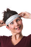 No more diets!!. Pretty brunette holding a measuring tape around her head and pulling a face with her tongue out Stock Photos
