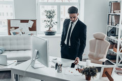 No more phone calls for today. Good looking young man in full suit laying his smart phone on the desk while standing in the office stock photography