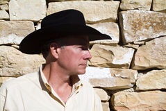 No Mortar. A man standing by a wall constructed of carefully placed cut stones and rock royalty free stock image