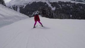 No movimento o esquiador lentamente e com cuidado esquiando abaixo de uma inclinação de montanha no inverno filme