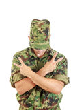 No name soldier standing with sign of peace with cross arms. Unknown soldier with hidden face in green camouflage uniform covers face with cap and standing with Stock Photos