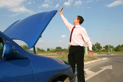 No network. Businessman searching for a mobile network in front of a broken car Stock Photos