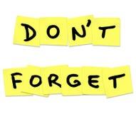 No olvide las palabras del recordatorio en notas pegajosas amarillas Fotos de archivo libres de regalías
