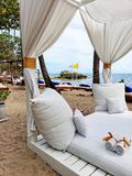 Four Seat Seaside Cabana. No one has yet arrived at this cabana. White curtains, pillows and towels laid out on a white deck. A small island in the sea can be royalty free stock image