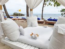Four Seat Seaside Cabana. No one has yet arrived at this cabana. White curtains, pillows and towels laid out on a white deck. A small island in the sea can be royalty free stock photography