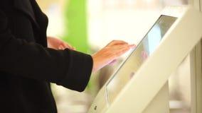 No outono mulher vestida que usa os auto-serviços terminais para pagar na tarifa vídeos de arquivo