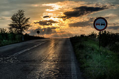 No overtaking sign by an old and damaged road Stock Photo