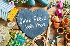 No pain, no gain concept with gardening tools. No pain, no gain german caption on heart-shaped stone among gardening tools royalty free stock photo