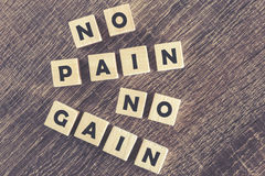 No Pain No Gain message. Written with wooden blocks on a wooden table royalty free stock photography
