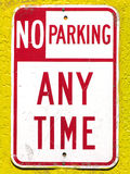 No Parking. A 'No-Parking' sign (red & white) nailed to a yellow wall Stock Photography
