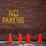 No Parking. Brick wall with no parking written on it.  Four orange pylons chained together are in front of the wall Stock Photography