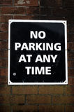 No Parking. Sign on Brick Wall Stock Photo