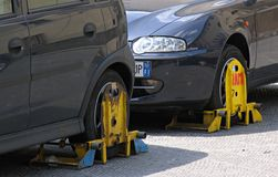 No parking. Wheel clamps on illegally parked vehicles Stock Photography