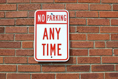 No Parking Any Time. A red and white sign affixed to a brick wall, stating that there is no parking permitted. Perfect as a metaphor for work environments Stock Image