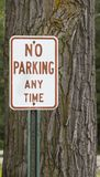 No Parking Anytime Sign. A sign stating no parking at anytime is posted next to a tree Royalty Free Stock Photo