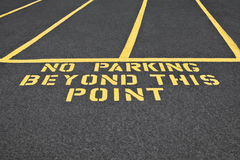 No Parking Beyond This Point. The parking lot has restricted areas and identified by the sign written on the asphalt Royalty Free Stock Photography