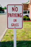 No parking on grass sign close up. A close up of a red and white no parking on grass sign on a residential street Royalty Free Stock Photography