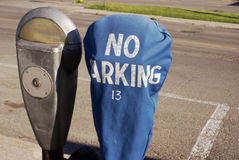 No Parking At This Meter. Closeup image of a no parking warning placed over top of a roadside parking meter Stock Image
