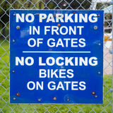 No Parking No Bikes Sign. A sign attached to a chain-link fence that reads: NO PARKING IN FRONT OF GATES / NO LOCKING BIKES ON GATES royalty free stock photos