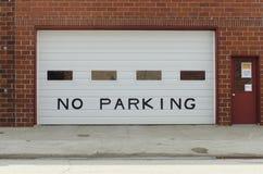 A garage door displays no parking sign. A garage door shows not to park royalty free stock photo