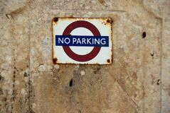 No parking prohibitory sign on a stone wall. Old worn metal sign with the text No parking. The prohibition sign hanging on a wall belonging to a stone house on Royalty Free Stock Photography