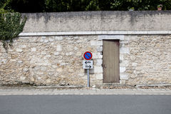 No parking sign against stone wall Stock Photo