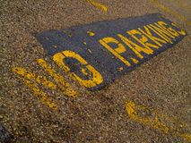 NO PARKING sign painted in yellow on pavement. A worn, weathered, and aged NO PARKING sign painted in yellow on patched, cracked pavement or asphalt in evening Stock Photo
