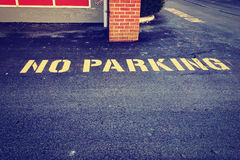 No parking sign on pavement in front of building Stock Photography