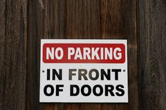 No Parking Sign post. Sign Post showing a warning of No Parking in front of doors Stock Photography
