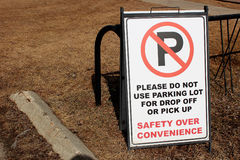 No Parking sign in a school staff lot beside some bike racks.  Stock Photo