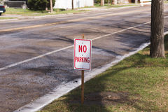 No Parking Sign on Street. White sign with & x27;& x27;NO PARKING& x27;& x27; on neighborhood street royalty free stock images