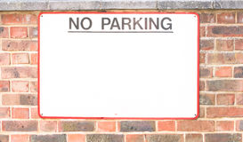 NO PARKING sign on very old brick wall Stock Photos
