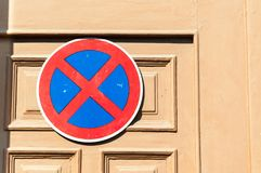 No parking sign on the wooden door to protect entrance from the car drivers . Stock Images