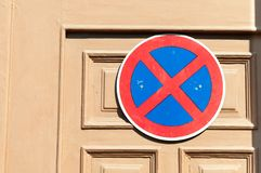 No parking sign on the wooden door to protect entrance from the car drivers. Stock Image