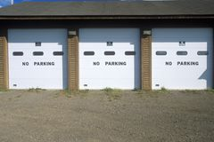 No Parking signs on a garage door Royalty Free Stock Image