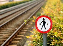 No pedestrian traffic. Battered no pedestrian traffic sign with a railroad track in the background Stock Image