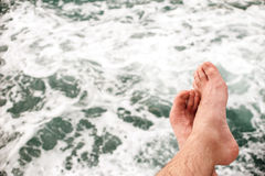 No person Unrecognizable man's legs, sitting on the edge of pontoon, outdoors against sea, texture Stock Photo