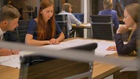 No pessoal moderno do escritório três na tabela olhe o papel de tiragem e fala vídeos de arquivo