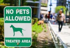 No pets allowed. Chicago, USA - May 24, 2014: Sign marking an area where no pets allowed. In the background a woman walking her dog Stock Photo