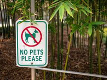 No pets please sign with dog crossed out hanging in a garden area royalty free stock photo