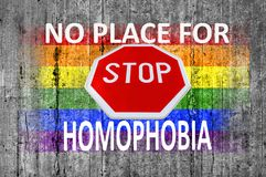 No place for homophobia and STOP sign and LGBT flag painted on gray concrete background stock photography