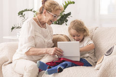 No place like grandma's home. Happy grandmother and her grandchild sitting on a sofa in a light home interior Royalty Free Stock Image